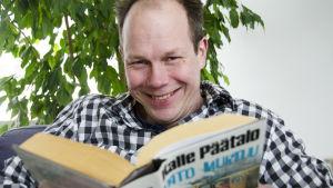 toimittaja Jukka Kuosmanen lukee Kalle Päätalon kirjaa Pato murtuu
