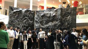 Grupperna samlas i museets aula framför en stor svart skulptur föreställande USAs landmassor och folk.