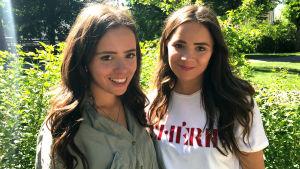 Två flickor med långt mörkt hår i en park