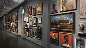 Massor med porträtt hänger på en lång vägg i Ateneum. En bild från samlingsutställning Historier inom finsk konst.