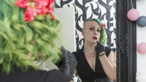 En kvinna med grönt hår står framför en spegel och förbättrar sitt läppstift.