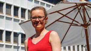 En kvinna i en röd top ståt ute i solskenet. Hon har glasögon på sig.
