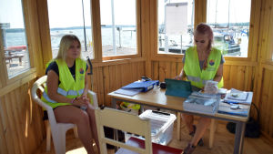 två flickor sitter invid fönster i hamn.