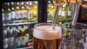 Två ölglas, med öl i ett av dem. I bakgrunden syns ölflaskor i kylskåp.