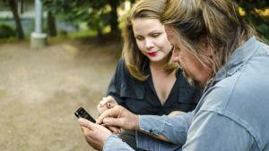 Kuusikymppinen mies ja aikuinen tyttärensä kännykän äärellä: Tytär neuvoo isää.