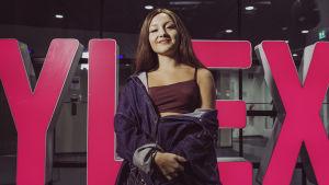 Laulaja ja räppäri Etta poseeraa YleX-kyltin edessä.