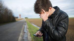 Ung man håller i en telefon.