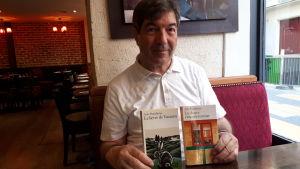 Den fransk-syrisk-svenske författaren Fawaz Hussain med en bok av Arto Paasilinna