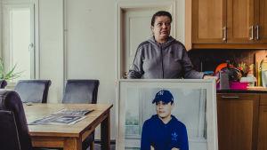 Carolina Sinisalo håller upp en stor tavla med sonen Robins foto.