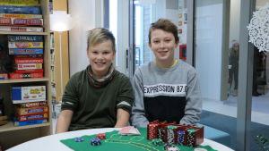 Två pojkar sitter vid ett bord. På bordet finns en kortpacke och pokerchips.