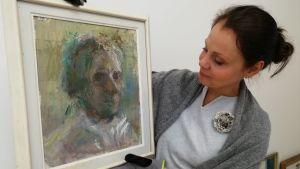 En kvinna håller i en tavla. Hon har handskar på händerna för att skydda konstverket. Kvinnan tittar på tavlan som föreställer en äldre kvina.