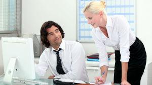 En snygg man och snygg kvinna på ett kontor som till verkar vara förtjusta i varann