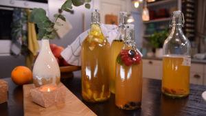 Kombucha i fyra glasflaskor på köksbordet.