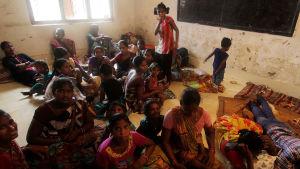 Fiskarfamiljer som på torsdagen sökt skydd i en skola i Konark, i Puri.