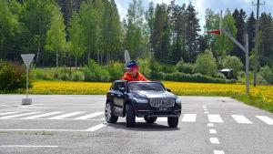En liten pojke som kör en leksaksbil.
