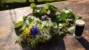 En halvfärdig blomsterkrans där små buketter av blåklint, björkris, prästkrage, allium och daggkåpa bundits på en björkkrans med hjälp av en tunn metalltråd.