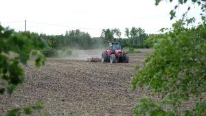 En traktor kör omkring på en åker.