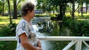 En kvinna står på en bro och tittar ner på en bäck.