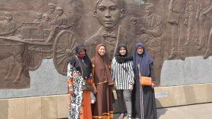Fyra kvinnor står framför stora bronsreliefer som berättar om Sukarnos liv.