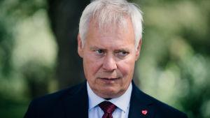 Antti Rinne i mörk kostym och röd slips mot en grön suddig bakgrund. Han har en sammanbiten min.