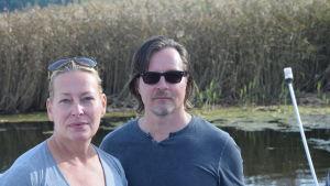 En kvinna och en man står på en båt vid en vassvik.