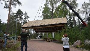 Ett tak lyfts upp från marken med lyftkran. Några människor fotograferar.