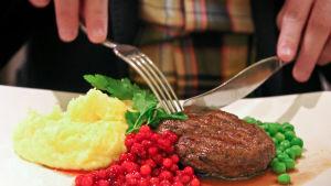 Människa äter biff med lingonröra och potatismos