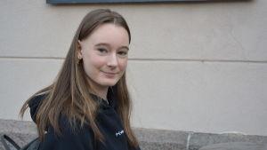 Wilma Rönnlund, en tjej i tonåren, med långt brunt hår, ler mot kameran.