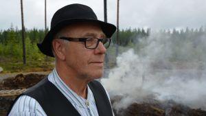 Man med hatt, rutig skjorta, väst och glasögon står utomhus.