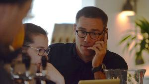 En man med glasögon talar i en mobiltelefon.