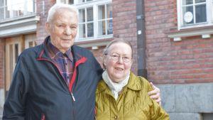 Ett äldre par, kvinna och man, står ute vid Ekenäs gågata och håller om varandra.