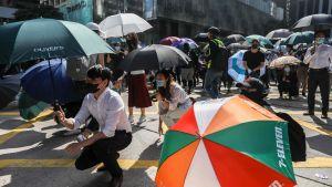 Personer som skyddar sig från tårgas med paraplyer i Hongkong.
