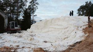 En stor snöhög med två människor som står ovanpå den. Till vänster en arbetsmaskin.