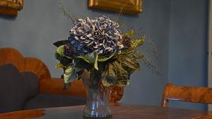 En blomma i en vas står på ett träbord.