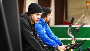 Jonathan IIlahti cyklar på spinningcykel tillsammans med vännen Victor Wik.
