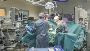 Kirurgit leikkaa potilasta leikkaussalissa.
