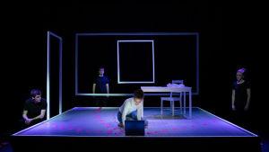 En ung kvinna sitter på knäna på en mörk scen och tittar ner i en datorskärm. Kring scenen står tre personer i mörka t-skjortor.