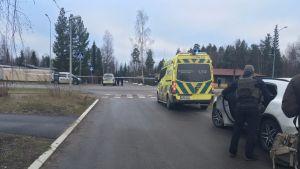 Poliser och en abulans har spärrat av ett område i Lahtis. En läkare med skottsäker väst syns på höger sida.