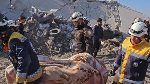 Medlemmar av frivilligkåren Vita hjälmarna bär bort dödsoffer efter flygattacken utanför Maaret Misrin. Bland dödsoffren ska det ha funnits åtminstone ett barn.