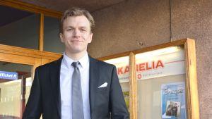 Alfred Backa, iklädd kostym står utanför dörren till kulturhuset Karelia i ekenäs.