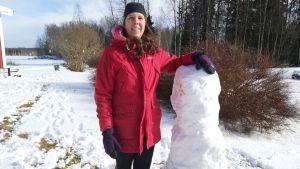 Kvinna ute bredvid snögubbe.