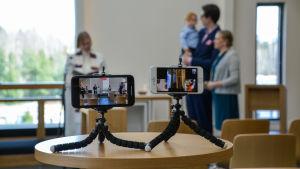 Två mobiltelefoner står på små stativ och filmar dopet.