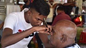 En barberare rakar en kund i Georgetown i Malaysia
