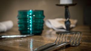 Haarukat veitset ja lasi ravintolan pöydällä.