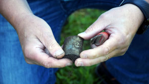 Ett par händer håller i ett nyuppgrävt metallföremål.