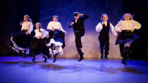 Sex ungdomar i svarta och vita kläder hoppar samtidigt på en teaterscen.