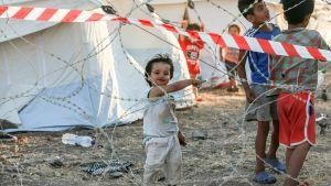 Barn som leker bakom taggtråd i flyktinglägret i Kara Tepe.