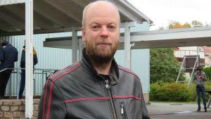 Portättbild på Johan Nilsson, en man med skägg,nästan utan hår på huvudet, klädd i svart skinnjacka. Står ute på en skolgård med några elever i bakgrunden.