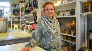 En kvinna i kassan i en affär.