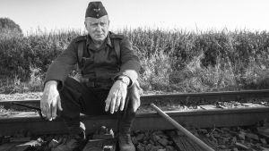En tysk soldat sitter och vilar på järnvägsskenorna.